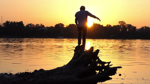 Young man stands on the tree roots on a lake bank in slo-mo Footage
