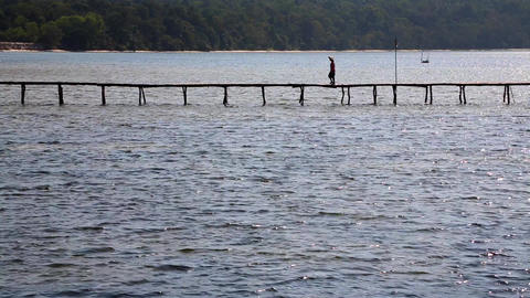 Silhouette of Person Walking on Wooden Walkway Above Water Archivo
