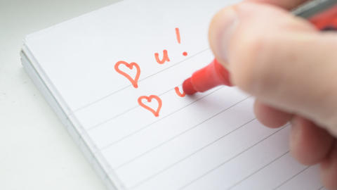 Hand writing I LOVE YOU U with red marker in notepad on white background Live Action