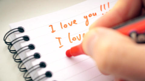 Hand writing I LOVE YOU many times with red marker Footage