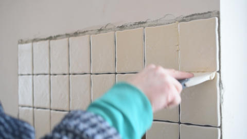 Tile worker filling gaps between tiles with grout Footage