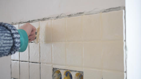 Tile worker filling crevices between tiles with grout Footage