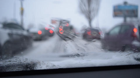 View through windshield on defocused scene on snowy city road Footage