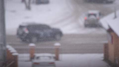 Snow falling in city on background of road Footage