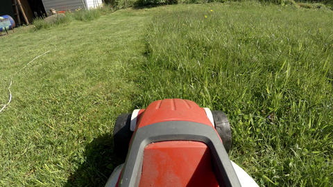 Electric lawn mower mowing the grass on the lawn. 4K Live Action