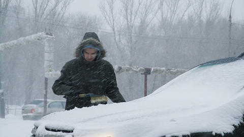 Man cleaning snow from car Archivo
