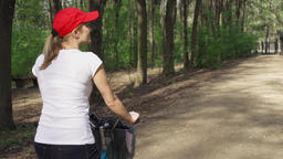 Slow Motion. Woman riding bike. Female teenager biking cycling in sunny park Footage