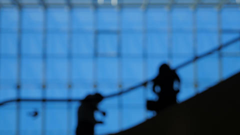 Blur people silhouettes on escalator moving inside of airport with large windows Footage