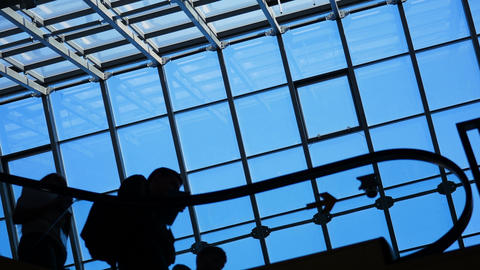 People silhouettes on escalator moving in shopping center with large windows GIF