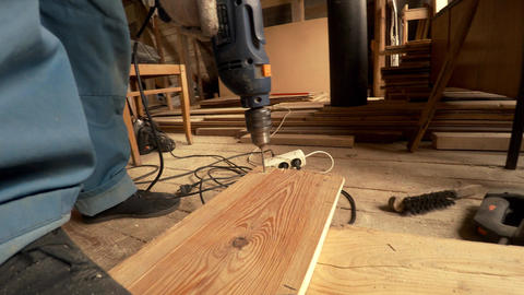 Carpenter with drill drilling a Board. 4K Footage