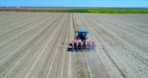 4K Aerial footage of a modern tractor plowing dry field, preparing land for Footage