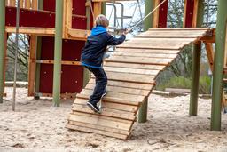 Happy boy climbing rope on the playground Fotografía