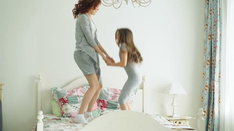 Happy cute daughter and young mother jumping and dancing on bed while have fun Footage