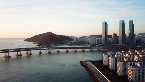 Gwangan Bridge and Haeundae aerial view at Sunrise, Busan, South Korea ビデオ