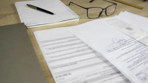 Documents, business diary, pen and eyeglasses lying on workplace in office Footage