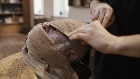 Barber covers face of senior man with hot towel before shaving Footage