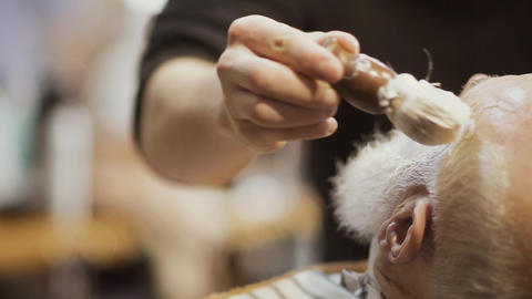 Barber applies shaving cream on face of old man and prepares skin to shaving Footage