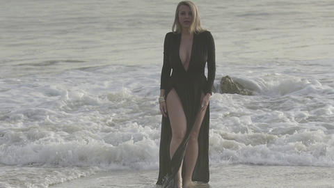 beautiful woman in a long black dress coming out of the ocean Footage