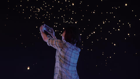 Asian Woman Photographs Sky Lanterns Rising Into The Night Sky Image