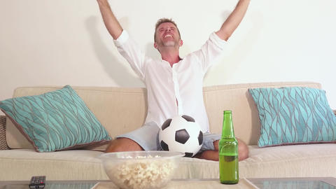 man watching football game on television enjoying a live match celebrating goal Footage