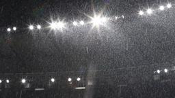 Snow falls over stadium lights GIF