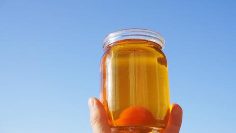 A honey jar against a blue sky background Live Action