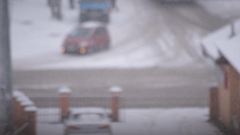 Snowing in city on background of road with cars and people Footage