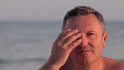 Man on the beach calmly looks in the camera and straightens hair. Man on the Footage