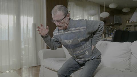 Old ill man suffering from lumber issue unable standing up holding his painful Live Action