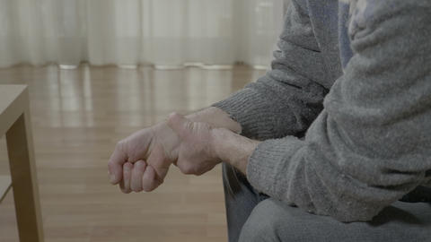 Closeup of old man with arthritis touching his painful wrist having rheumatism Footage
