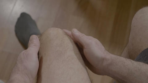 Point of view of mature man with rheumatic pains on legs sitting on bed and Footage