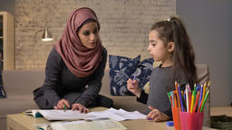 Young beautiful mother in hijab doing homework with her little daughter Footage