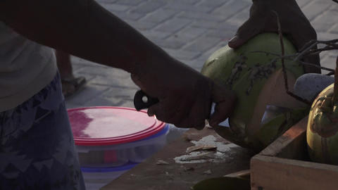 Man cuts off pieces from a young fresh coconut. Maldives video side view Archivo