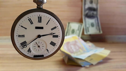 Clock and Money. The Clock Revolves Against The Background Of Currency Bills Footage