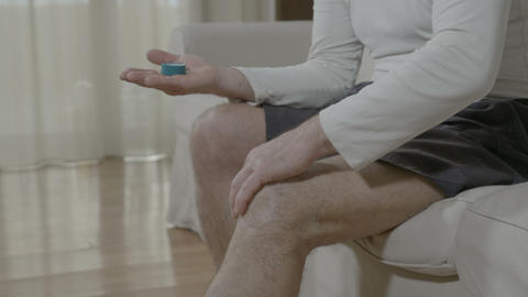 Body care and therapy massage with medicinal cream of elderly man with knee pain Live Action