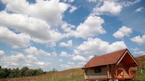 white clouds on the blue sky over the wooden house Footage