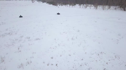 View from the height of ATVs riding through the snowy landscape in winter ビデオ