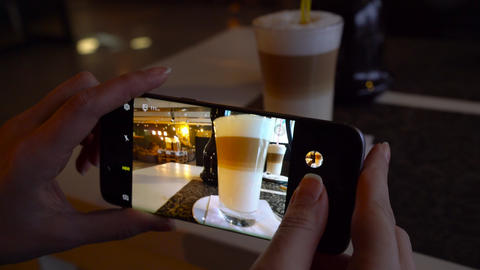 Girl makes a photo of a latte on a smartphone in a cafe close up Archivo