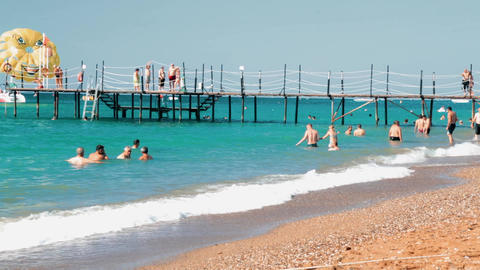 Beach full of people in a sunny day. People on the beach are swimming in sea Archivo
