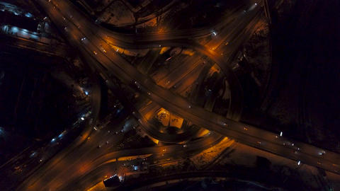 Vertical top down aerial view of traffic on freeway interchange at night, fast Footage