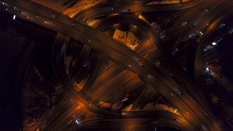 Vertical top down aerial view of traffic on freeway interchange at night Footage