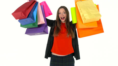 Female shopper holding multicolored shopping bags on white background in studio Archivo