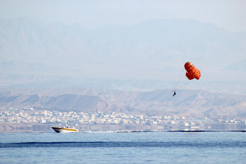 orange paraglider with a cheerful pattern hanging over a boat Photo