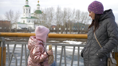 Little daughter eating yummy hot dog and talking with mother in winter Footage