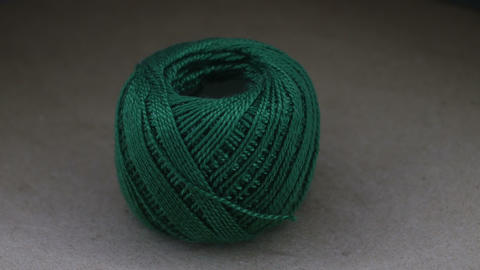 Ball of green yarn wool on rotating table Live Action