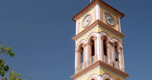 Establishing shot of the clock tower of the Parroquia de la Santa Cruz in Puerto GIF