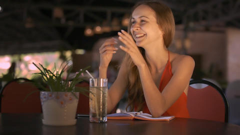 Girl Sits at Table Smiles Listening to Friend Story Footage