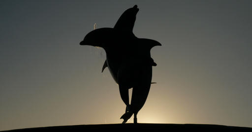 Silhouette of a dolphin fountain statue at dusk or sunset against the sky Footage