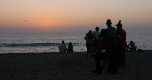 Couples, musicians, and tourists watching and enjoying a picturesque sunset at Footage