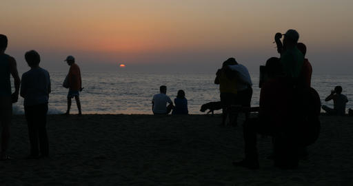 Silhouettes of people enjoying the sunset together on the beach including Footage